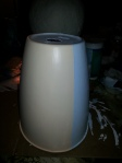 """Take a plastic flexible garbage can and squash it a bit for correct shape. Cut a hole at top that will accomodate a 1"""" PVC pipe. Use primer paint on all and let dry. Place painter's tape down half vertically. Use outside acrylic peach on one side, grey on other side."""