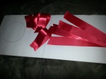 Get a roll of red ribbon, cut several pieces that you will fold over and hot glue each end. Cut a circle out of white foam board.