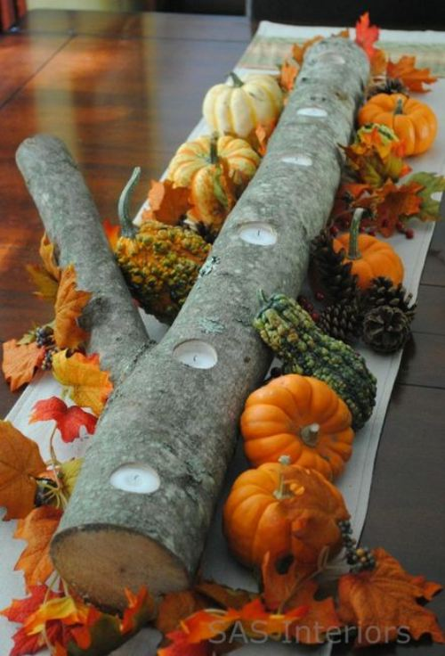 Simplicity at its best: Nature, harvest, and candles come together with a log with holes drilled for candles and accented with leaves, gourds, and mini pumpkins. Image courtesy of The Berry and SAS Interiors.